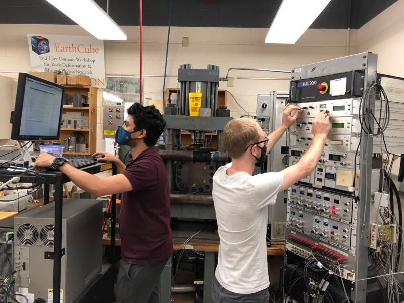 Two grad students a series of tests on fractured rock using acoustic vibrations that simulate seismic activity.